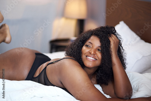 Fototapeta adorable fat sexy african woman lie on bed at home, have rest, enjoy, relax time
