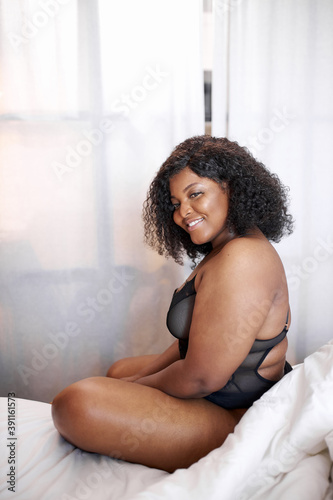 Obraz na plátně adorable afro woman smile sitting on bed, has happy day, enjoy being fat, she ha