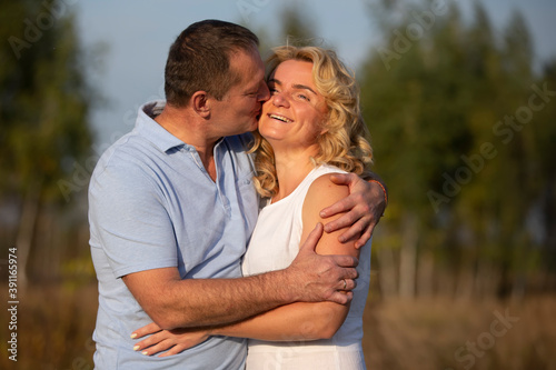 A beautiful middle-aged couple in love hugging and kissing.