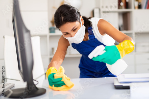 Papel de parede Positive young kazhahstani woman wearing uniform and mask cleaning at company office