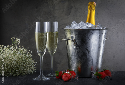 Champagne bottle in bucket with ice and glasses of champagne on dark background Fotobehang