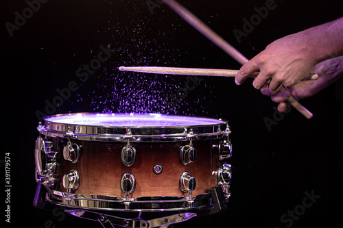 Fotografia Drum sticks hitting snare drum with splashing water on black background under studio lighting