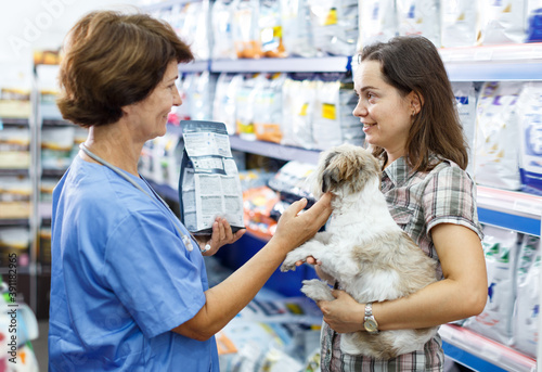 Fine mature woman veterinary consulting female client with cute havanese about p Fototapet