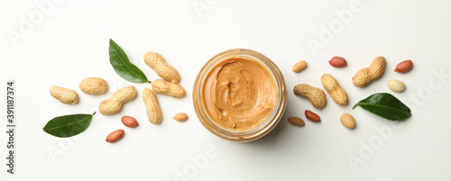 Canvastavla Jar with peanut butter, peanut and leaves on white background