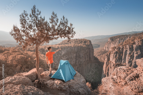 Foto Man hiker or extreme climber stands near camping tent on a cliff viewpoint at the deep Tazi canyon in Turkey