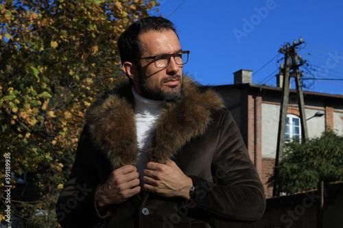 Fototapeta Przystojny mężczyzna w okularach i płaszczu z futerkiem. obraz