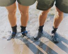 Man And Woman Wearing Waterproof Booties, Standing In Surf
