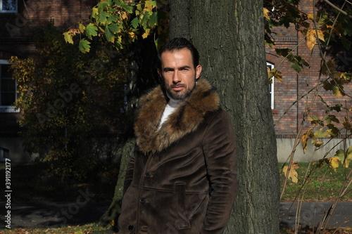 Obraz Mężczyzna 40 plus w płaszczu w piękny jesienny dzień. - fototapety do salonu