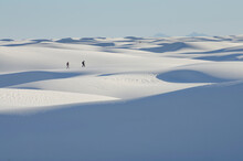 Two People At A Distance Walking Across White Sand Dunes.