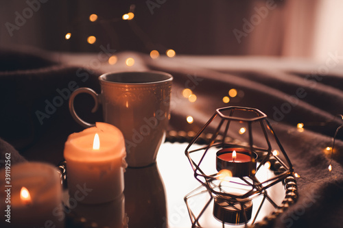 Fotografia Cup of hot tea with burning candles on tray in bed over Christmas lights close up