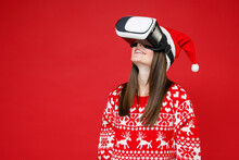Smiling Young Santa Woman 20s Wearing Sweater Christmas Hat Watching In Vr Headset Gadget Isolated On Bright Red Colour Background Studio Portrait. Happy New Year Celebration Merry Holiday Concept.
