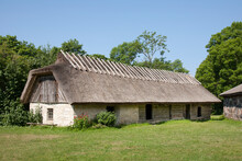 Muhu Museum Exterior In Estonia, A Barn With A Thatched Roof.