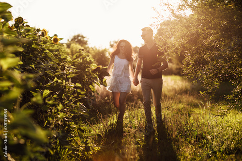 Beautiful couple having fun in sunflowers field. A man and a woman in love walk in a field with sunflowers, a man hugs a woman. selective focus