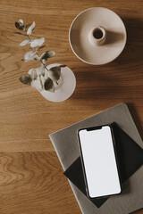 Fototapeta Tenis Flatlay of blank screen smart phone, notebook, eucalyptus branch on wooden background. Home office desk workspace. Business, work template. Flat lay, top view.