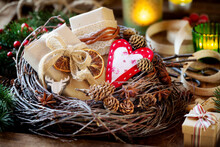 Eco Friendry Zero Waste Gift Wrapping Concept. Beautiful Xmas Presents In Brown Kraft Paper Decorated With Dried Oranges, Pine Cones And Burlap Ribbon With Lit Candles At The Background