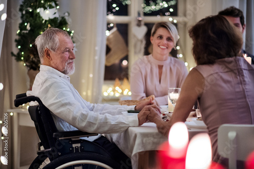 Senior man in wheelchair with family indoors celebrating Christmas together Canvas