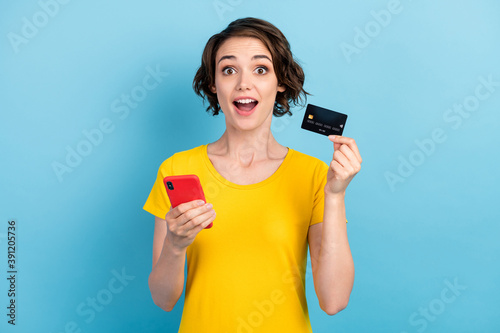 Photo of lovely amazed lady hold telephone credit card open mouth wear yellow t-shirt isolated blue color background