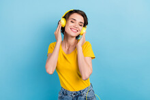 Photo Of Charming Young Girl Closed Eyes Listen Music Wear Headphones Yellow T-shirt Isolated Blue Color Background