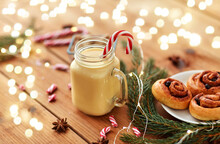 Christmas And Seasonal Drinks Concept - Eggnog In Glass Mug With Candy Cane Decoration, Cinnamon Buns, Fir Tree Brunch And Garland Lights On Wooden Background
