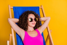 Photo Portrait Of Relaxed Woman Lying In Blue Lounge Chair With Hands Behind Head Wearing Glasses Pink Bikini Isolated On Vivid Yellow Colored Background