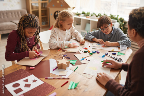Obraz Multi-ethnic group of children making handmade Christmas cards together while enjoying art and craft class, copy space - fototapety do salonu