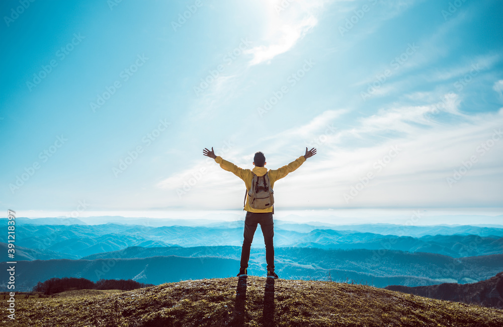 Fototapeta Successful man with arms up on the top of the mountain - Hiker on the cliff raising hands to the sky.