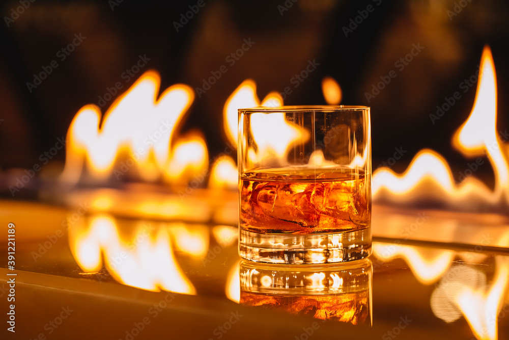 Fototapeta side view of glass of whiskey with ice on a background of a burning flame
