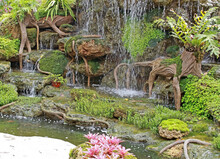 Large Man Made Waterfall Garden Feature Decorated With Tropical Plants And Palms, Southeast Asia.