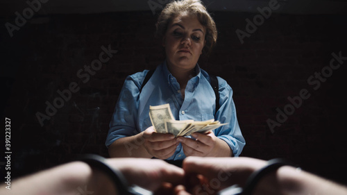 Fotografija Close up of suspect hands in handcuffs giving money to female police officer as
