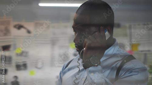 Fototapeta View through window louvers of afro policeman talking on phone during work at po