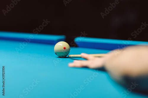 Hand with cue stick on blue billiard table with ball Fototapet