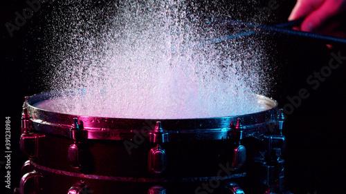 Freeze motion of drummer hitting drum with water splashes Fotobehang
