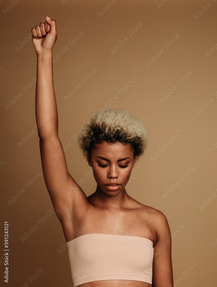 Fototapeta African american woman standing with raised arm
