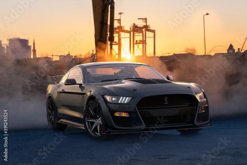 Ford Mustang Shelby GT500 drifting in a parking lot in an industrial area