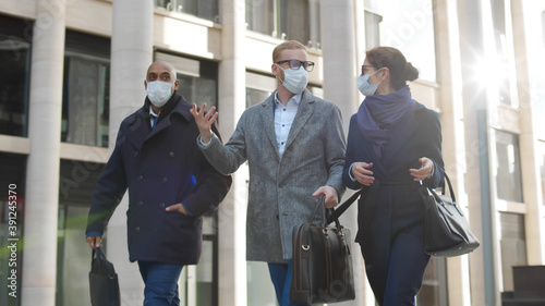 Obraz Group of colleagues in formal suit and safety mask walking together past city building outdoors - fototapety do salonu