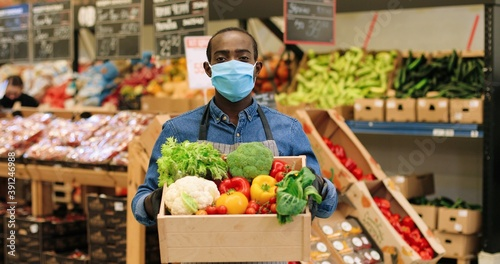 Fototapeta Portrait of joyful male food store manager in mask and gloves standing in supermarket and holding box with fresh vegetables, looking at camera and smiling