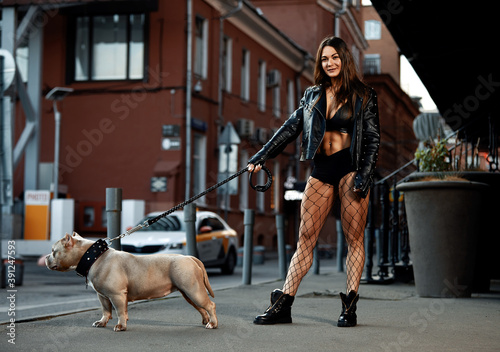 Obraz Sexy and srong brunette woman posing with bully dog on city street, looking at camera. - fototapety do salonu