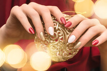 Christmas Nail Design. Female Hands With Red And Golden Manicure. Female Hold Golden Xmas Toy Orb. Happy New Year.