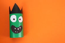 Funny Green Monster On Orange Background, Top View With Space For Text. Halloween Decoration