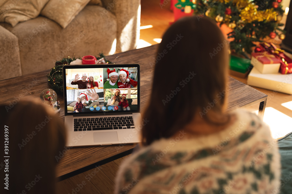 Fototapeta Caucasian woman with her daughter at christmas on a video call