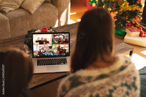Obraz Caucasian woman with her daughter at christmas on a video call - fototapety do salonu