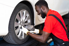 Black Man Mechanic Working Under A Vehicle In A Car Service Station. Expertise Mechanic Working In Automobile Repair Garage.