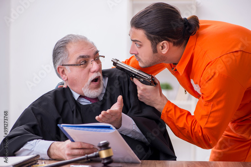 Fotografia Old male judge meeting with young captive in courthouse