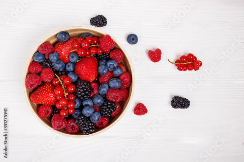 Fototapeta Mix of berries in bowl on white wooden background