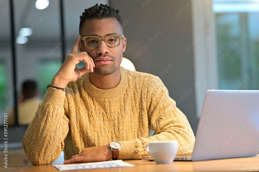 Fototapeta Portrait of african american trendy guy working from home on laptop