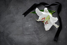 Flat Lay Of Lily Flowers And Black Ribbon. Funeral Symbol
