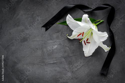 Obraz na płótnie Flat lay of lily flowers and black ribbon. Funeral symbol