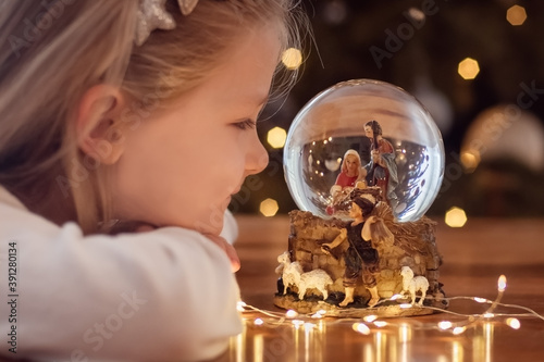 Girl looking at a glass ball with a scene of the birth of Jesus Christ in a glas Canvas