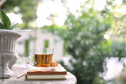 Red tea in transparent glass with plant pot and notebook Fototapet