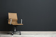 Leinwandbild Motiv Comfortable office chair near black wall indoors. Space for text